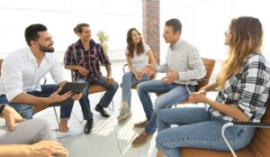 A photo of a team sate in a circle discussing well-being