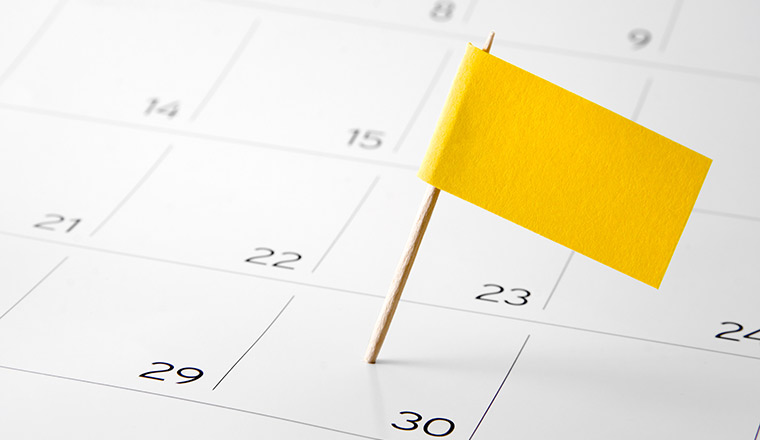 A yellow flag is placed on a calendar