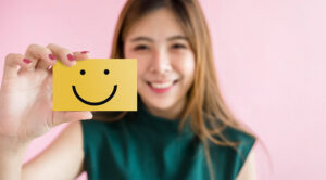 Happy person holds up a post it note with a smiley face on it