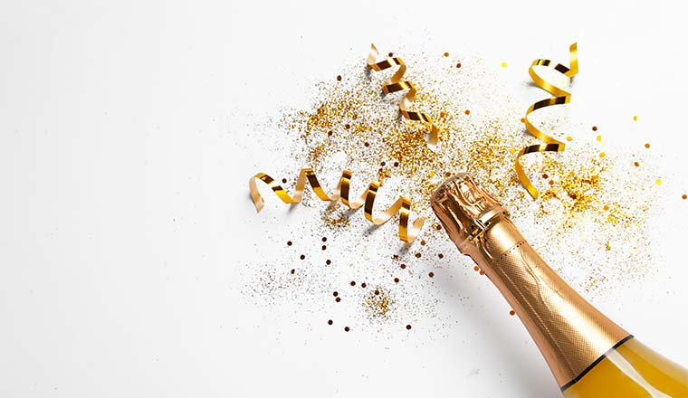 A photo of a champagne bottle with gold confetti