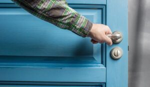 A photo of a man closing a blue door