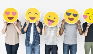 A group of people hold emoticons over their faces