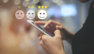 A person on a phone selects a happy face with 3 stars
