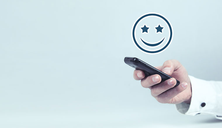 A photo of a smiley emoji above a mobile phone