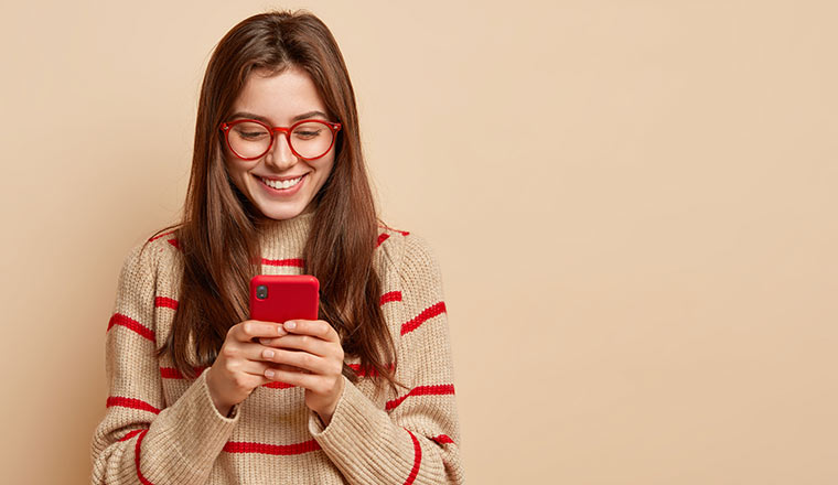 A woman wearing red glasses smiles as she looks at her phone