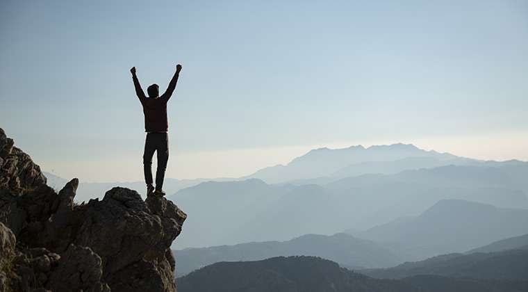 A man stands on a rock with his hands punched in the air