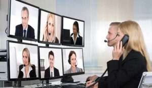 A woman on the phone talks to a group of people on different monitors