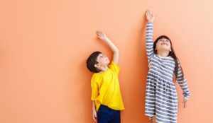 A photo of children reaching to measure