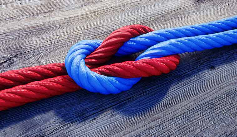 A red and a blue rope are tied togetherin a reef not