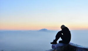 A photo of someone in consideration while looking across mountain range