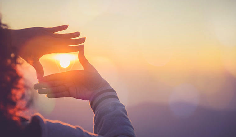 A photo someone using their hands to frame the sun