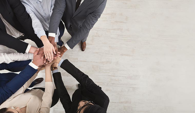 A picture of a group of people putting their hands together