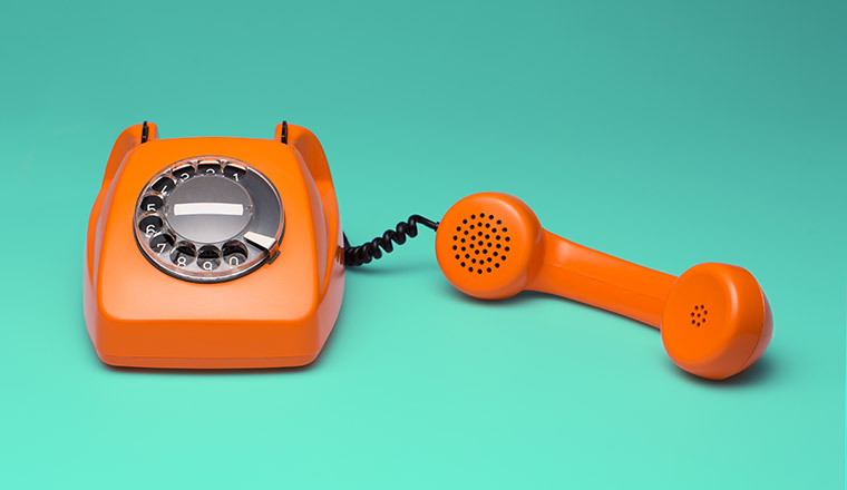 An orange old fashioned telephone