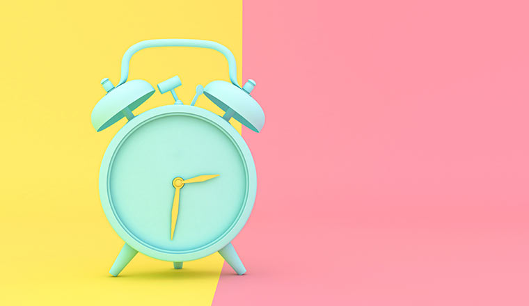 A green clock is against a yellow and a pink background