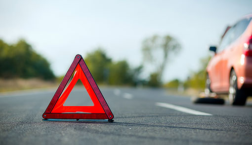 A photo of a red triangular sign next to a car puncture