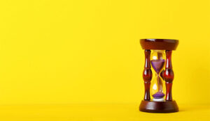 A photo of an hourglass on a yellow background