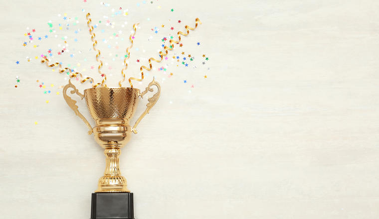A golden cup has confetti exploding out of it