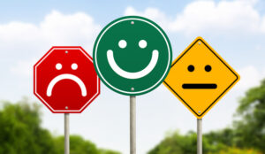Three traffic signs have faces on them. The one on the right is red and unhappy, the one in the middle is green and happy and the one on the left is yellow and average