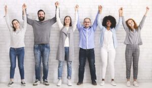 A photo of a group of people holding their hands in the air