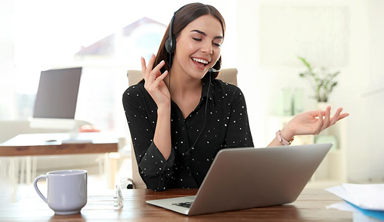 A woman with a headset on, talks animatedly in front of a laptop