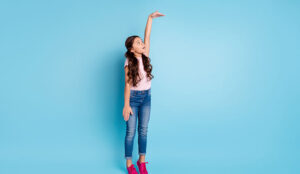 A picture of a girl measuring height with arm