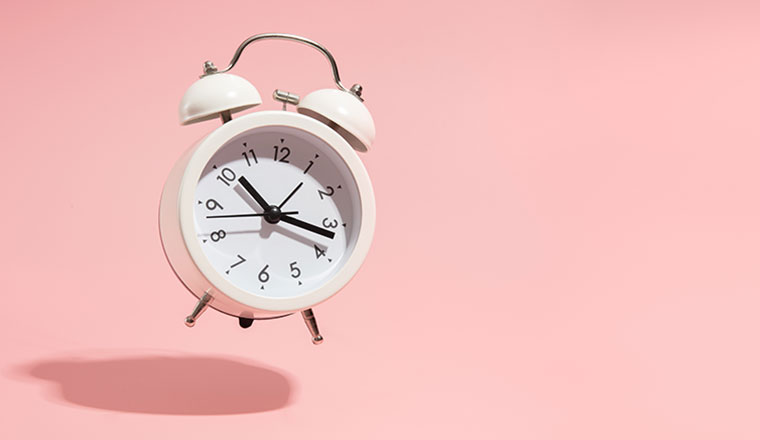 An alarm clock showing 20 past ten on a pink background