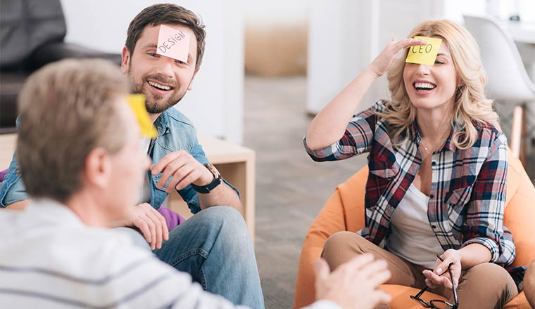 A photo of colleagues playing a game with post-it notes