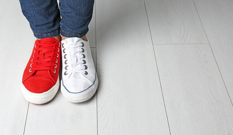 A person wearing jeans and a red shoe and a white shoe