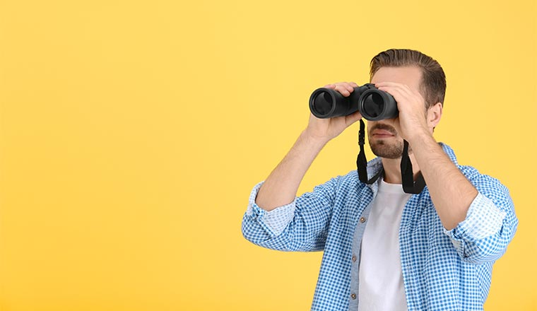 A photo of someone holding binoculars infront of their face