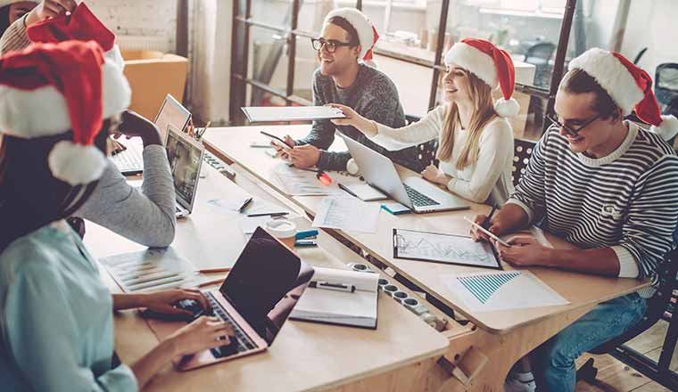 A picture of office workers wearing Christmas hats