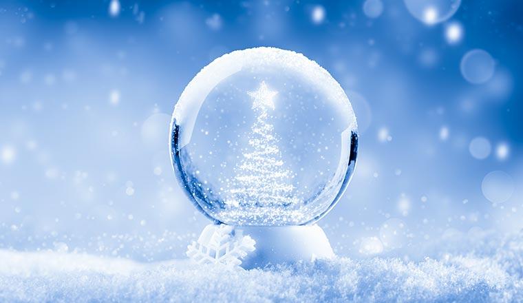 A snow globe on a blue background with a snowy Christmas tree shape inside