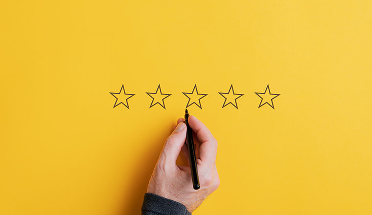 A photo of a hand drawing five stars