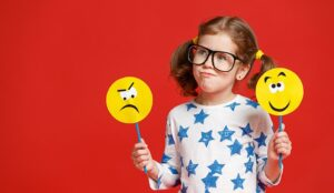 A girl holds to emoji faces- one is angry and the other is smiley