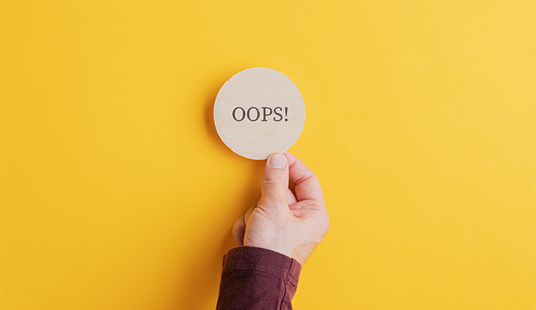 """A photo of the word """"oops"""" in a wooden circle"""