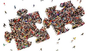 A picture of people grouped together to form a puzzle shape