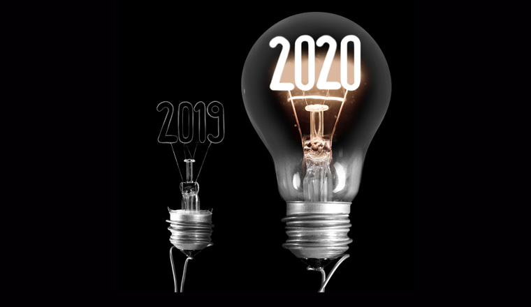 Two lightbulbs in contrast with a black background. One has 2020 lit up, and the other has 2019 in the background