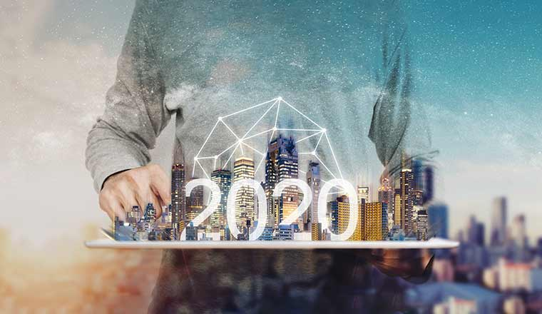 A picture of a small scale city with the word 2020, with a person stood next to it