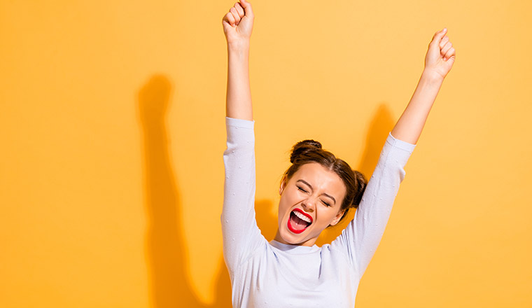 A photo of a person celebrating with hands in the air