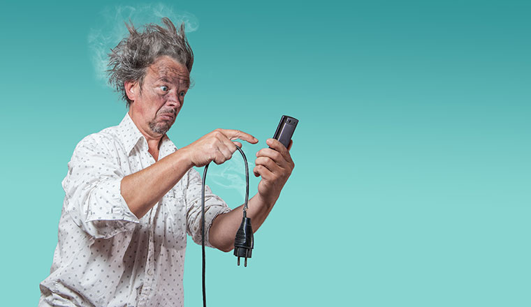 A picture of a man experience a bad electric shock on the phone