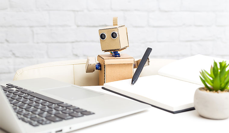 A photo of a cardboard robot holding a pen and looking at a laptop
