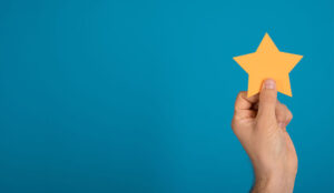 A photo of someone holding a yellow star against a blue background
