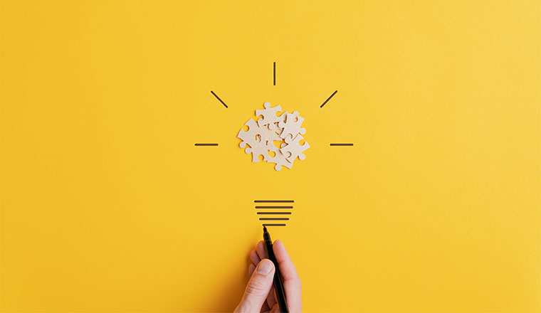 A photo of a light bulb made from puzzel pieces