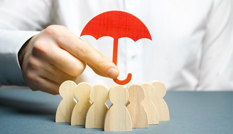 A photo of a red umbrella being held over wooden figures