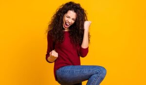 A woman fist pumps with joy
