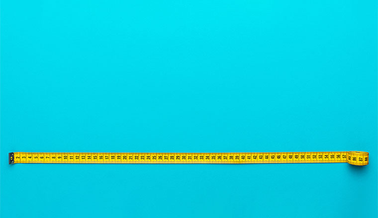 A photo of a yellow measuring tape on a blue background