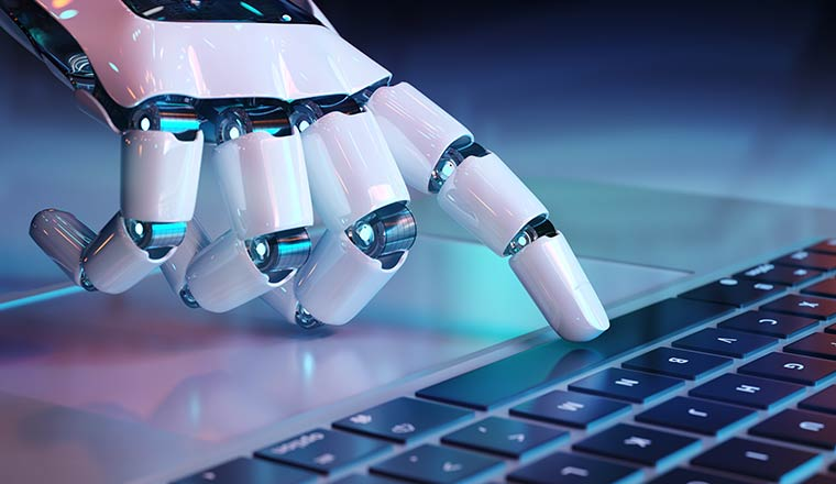 A picture of a robot hand pointing at a computer keyboard