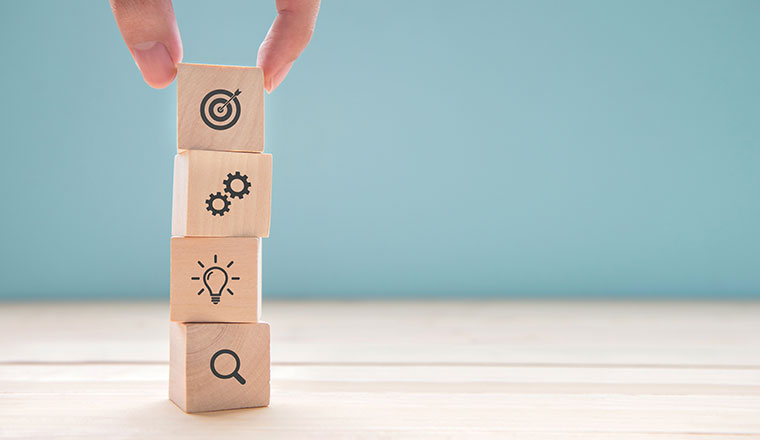 A photo of blocks being stacked with strategy symbols