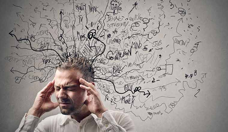 A picture of a person holding his head and surrounded by lots of thoughts