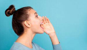 A lady hold her hand up to her mouth while yelling. There is a light blue background