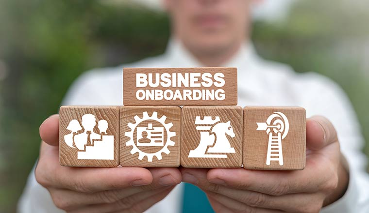 A picture of a person holding blocks that depict an onboarding process
